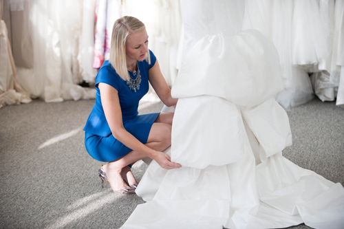 Project Runway alumni Heidi Elnora fiddles with a wedding dress on her new show, Bride by Design, on TLC Entertainment.