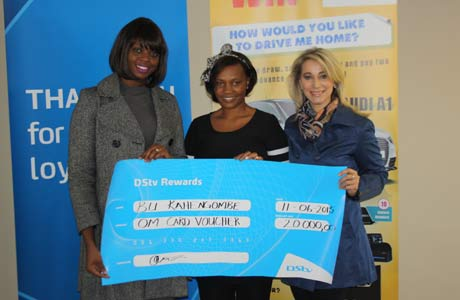 Sulvia Kahengombe, receiving a voucher on behalf of her husband, as the winner of a MultiChoice Namibia competition, with Manga Nawa-Mukena, marketing manager of MultiChoice Namibia, and Deneil Aspeiling